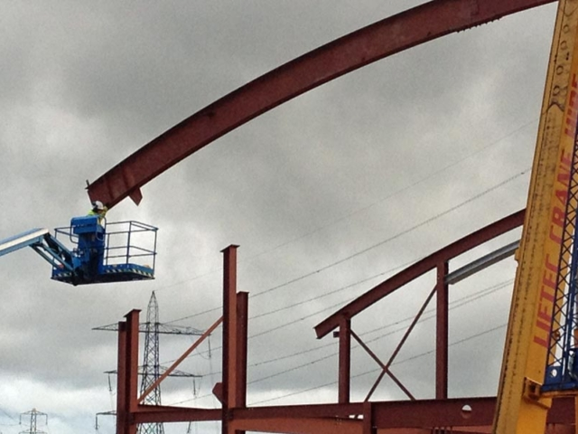 moving curved steel roof beam into place north kent community church